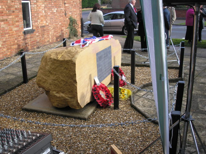 Memorial stone, dedicated and unveiled, first wreathes and items of remembrance laid upon it. | Ian Byrnes